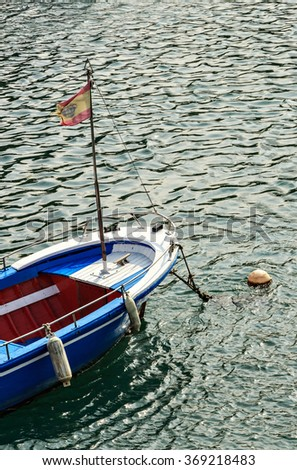 Blue boat with flag in San Vicente de la Barquera, Cantabria, Spain.Vertical image.