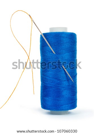 blue bobbin thread with needle and sewing pin isolated on white - stock photo