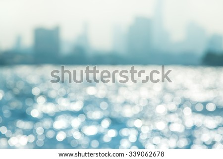 Blue bokeh on the water with shadow city landscape - stock photo