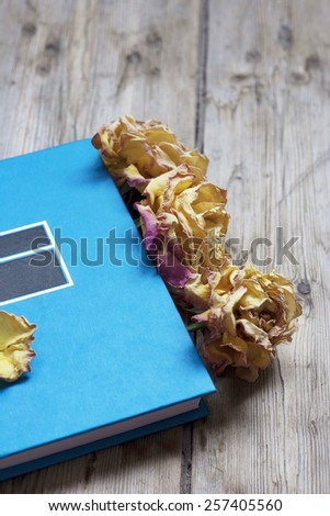 Blue book on the wooden floor with dry roses - stock photo