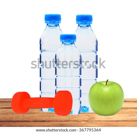 Blue bottles with water, dumbell and green apple on table isolated on white background - stock photo