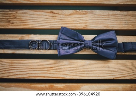 blue bow tie and wedding rings - stock photo
