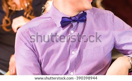Blue bow tie with purple shirt  closeup - stock photo