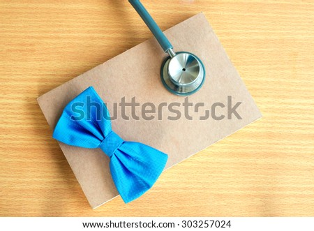 Blue bow with stethoscope  close up on notebook. - stock photo