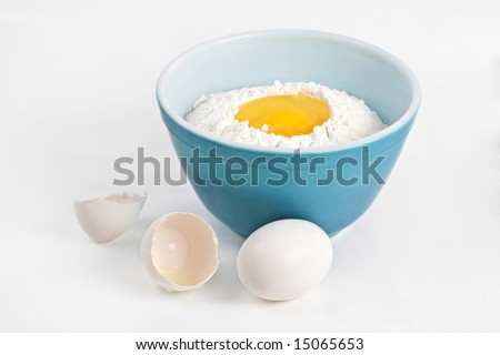 blue bowl filled with flour and broken eggs