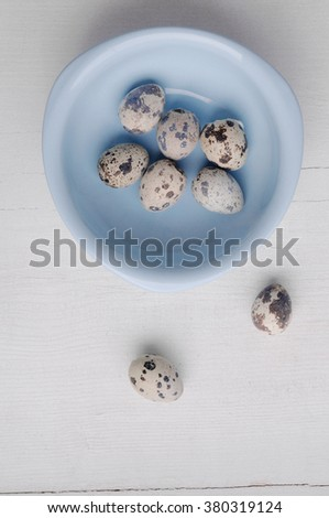 Blue bowl with fresh quail eggs on wooden background