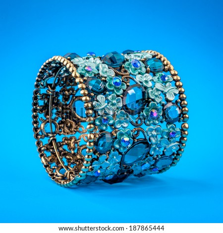Blue braclet with gems on color background - stock photo