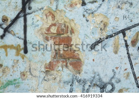Blue brick wall graffiti. Blue stone wall old plaster . Old brick wall cracks and holes . gouges in the stone wall . black letters on a blue wall - stock photo