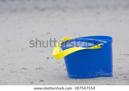 blue bucket abandoned at the beach full of water from the last high tide - stock photo