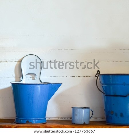 blue bucket, ewer and cup on grunge wall
