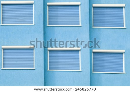 Blue Building Facade with Six Closed Windows Shutters Background with Space for Text or Image - stock photo