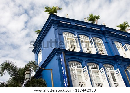 Blue building with white shutters and windows. China Town, Singapore - stock photo