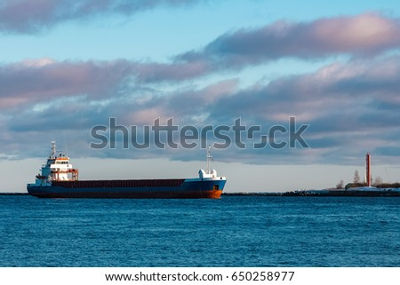 Blue bulk carrier sailing in still water