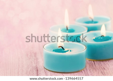 Blue burning candles on romantic pink vintage wooden background with blurred boked for copy space