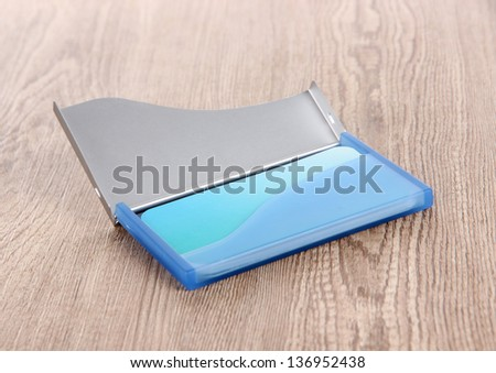 Blue business card holder on wooden background - stock photo