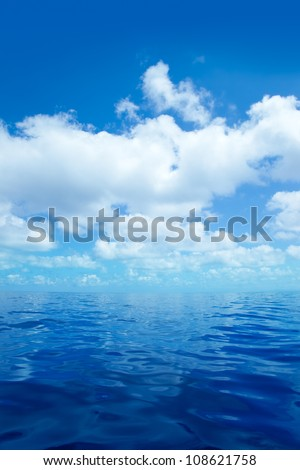 Blue calm sea water in offshore ocean with clouds mirror surface - stock photo