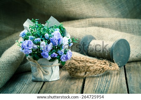 blue Campanula terry flowers in paper packaging, on wooden background - stock photo