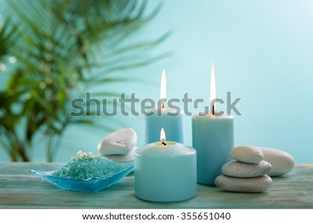 Blue candles with spa salt on table