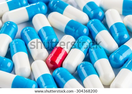 blue capsules and red capsules, illness medication cure pharmaceutical close up - stock photo