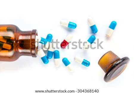 blue capsules and red capsules with  bottle, healthcare and medicine medication cure - stock photo