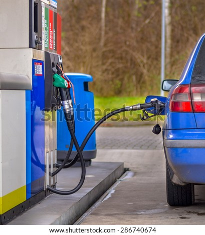 Blue car filling up with fuel at the gas station against inflated prices - stock photo