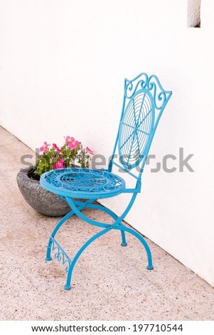 Blue cast iron cafe style chair next to a plant pot with flowers in it. - stock photo