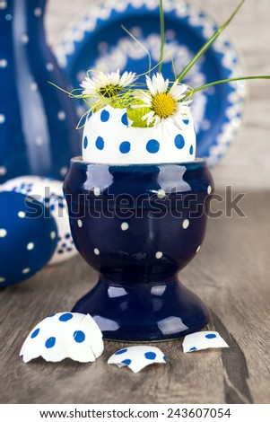 Blue ceramic Egg holder with flowers in egg shell and matching ceramics on wooden table. Happy Easter! - stock photo