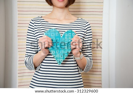 Blue ceramic heart in woman hands