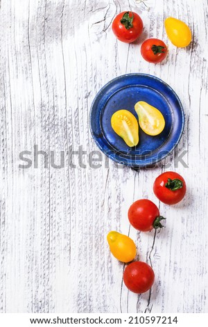 Blue ceramic plate with mix of red and yellow cherry tomatoes over white wooden table. Top view. See series. - stock photo