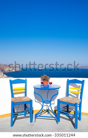 Blue chairs and table on a mediterranean balcony with nice view to the sea, Santorini, Greece - stock photo