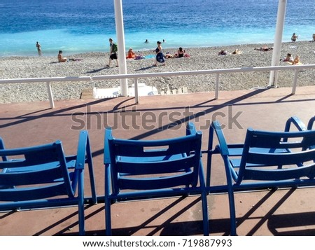 Blue chairs on the Promenade des Anglais in Nice, France.