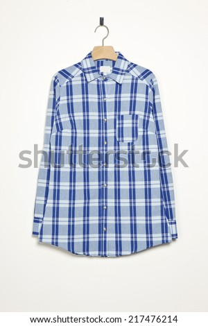 Blue check pattern shirts with wood hanger isolated white. - stock photo