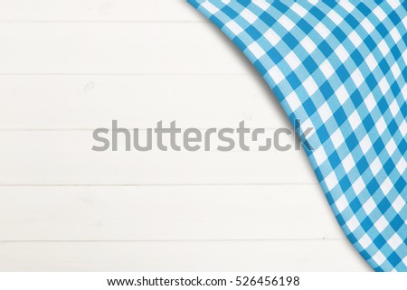 Blue checkered tablecloth on blank white holiday wooden surface