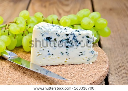 Blue cheese, grapes, knife on background wooden board - stock photo