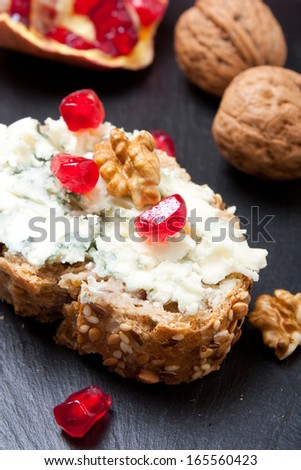 Blue cheese on a slice of grain bread with pomegranate and nuts