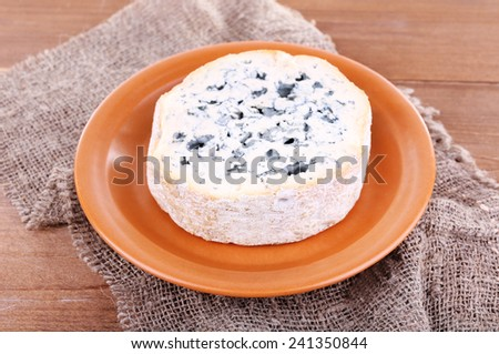 Blue cheese on earthenware dish on burlap cloth and wooden table background - stock photo