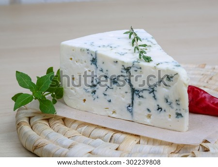 Blue cheese on the wood background with basil leaves - stock photo