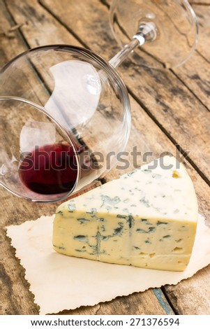 Blue cheese on vintage paper with overturned wineglass on wooden table. Restaurant wine list background.  - stock photo