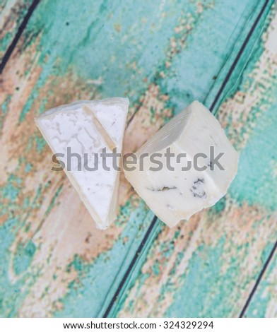 Blue cheese slices over wooden background