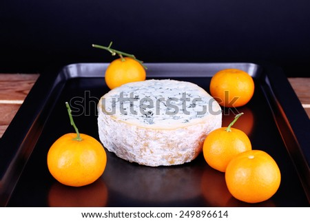 Blue cheese with oranges on metal pan and dark background - stock photo