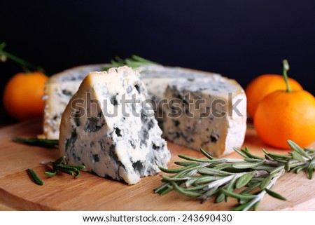 Blue cheese with sprigs of rosemary and oranges on wooden board and dark background - stock photo