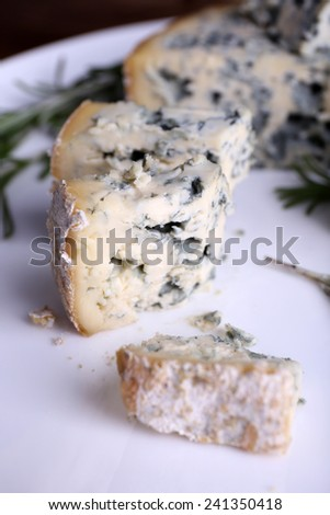 Blue cheese with sprigs of rosemary on plate, closeup view - stock photo