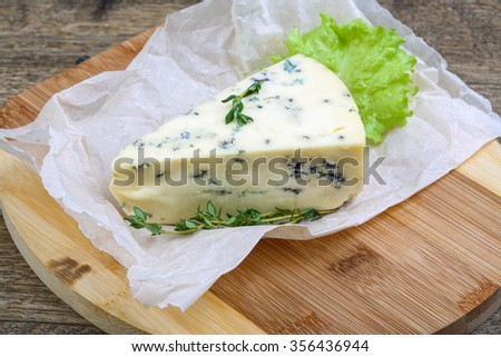 Blue cheese with thyme and salad leaves - stock photo