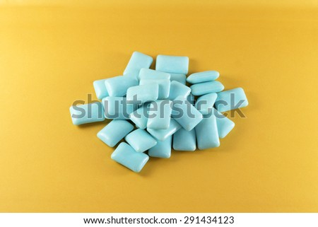 Blue chewing gum on yellow background