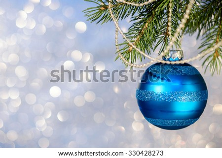 Blue Christmas ball on a Christmas tree branch over blurred shiny background, close up. Selective focus.