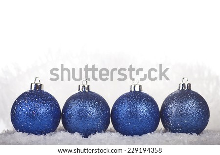 Blue Christmas balls in the snow on a white background. - stock photo