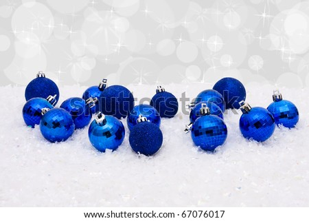 Blue christmas balls on a snow and white background, christmas time