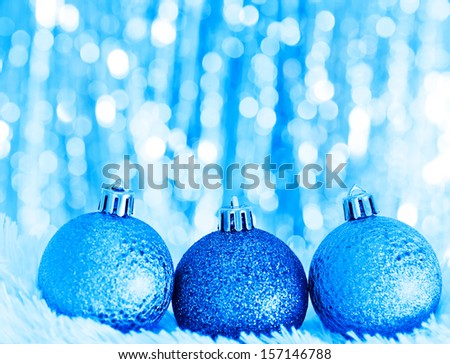 blue christmas balls on white fur and  lights  - stock photo