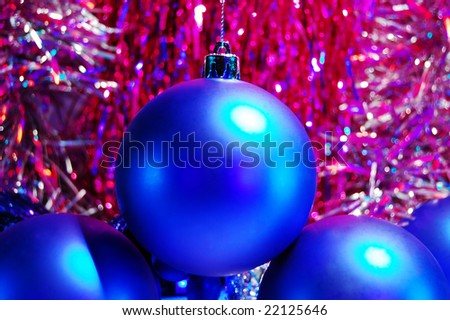 Blue Christmas baubles and crimson tinsel - stock photo