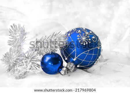 Blue Christmas baubles with silver ornament on neutral winter background, text space, Shallow DOF, focus on crown of bigger ball. - stock photo